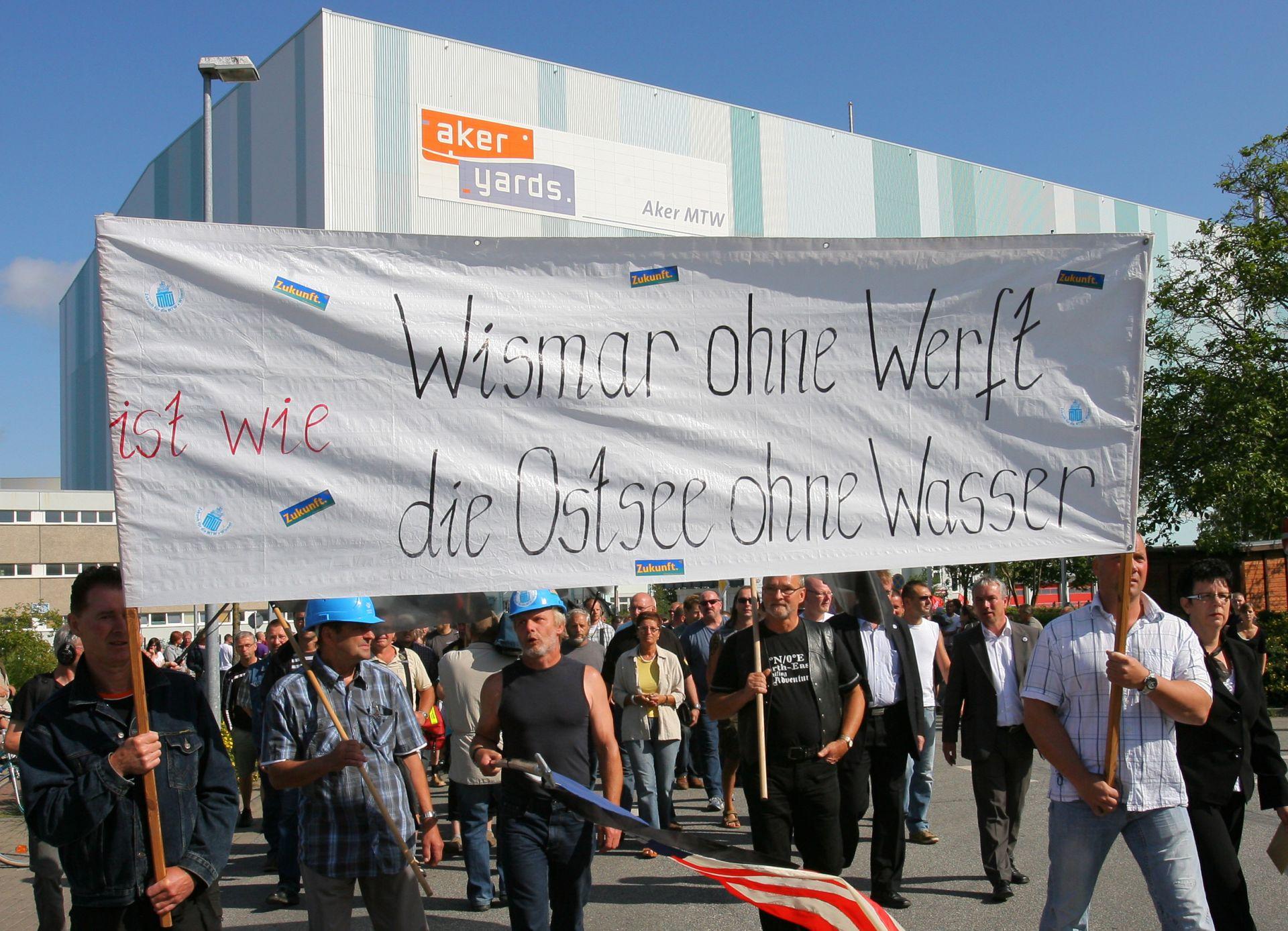 Vor der Wadan-Werft in Wismar sammeln sich am Freitag (31.07.2009) die Werftarbeiter für eine anschließende Demonstration. Rund 1.500 Menschen beteiligen sich an dem Zug durch die Hansestadt, um auf das Drama an den Wadan-Standorten aufmerksam zu machen. Vom kommenden Montag (03.08.2009) an wird die Arbeit auf den insolventen Wadan-Werften in Wismar und Rostock-Warnemünde ruhen. In den geplanten Beschäftigungsgesellschaften sollen dann die noch 2.400Wadan-Arbeiter aufgefangen werden, wenn die notwendigeZustimmungsquote von 95 Prozent erfüllt wird. Foto: Bernd Wüstneck dpa/lmv/lno (zu dpa 0348 und 0491 vom 31.07.2009) +++(c) dpa - Report+++